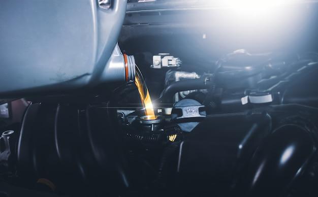 Meccanico che versa olio lubrificante nel motore dell'auto per la manutenzione del veicolo
