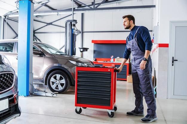 Meccanico che spinge la scatola con gli strumenti e si prepara a risolvere un problema con l'auto mentre si cammina nel salone dell'auto.