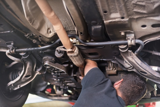 Meccanico che ripara il sistema di scarico