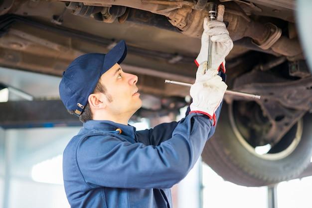 Meccanico che ripara un'auto sollevata