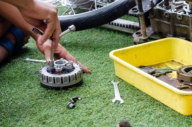 Meccanico che ripara un motore del motociclo