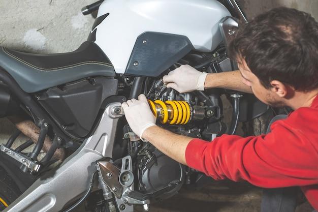 Riparatore meccanico che fa manutenzione o riparazione, fissaggio su moto, moto, centro assistenza