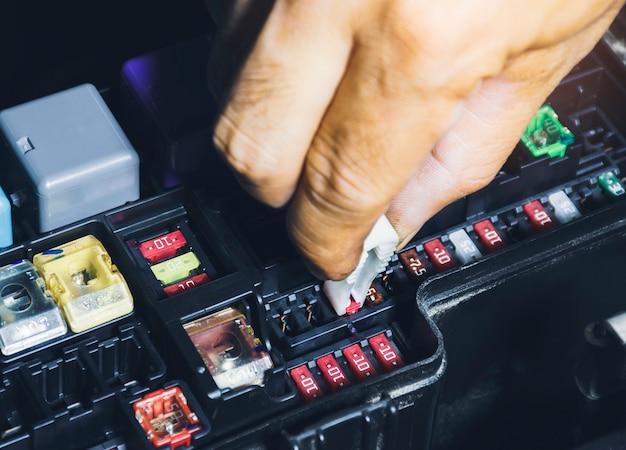 Il meccanico sostituisce il fusibile di ricambio nella scatola dei fusibili dell'auto con lo strumento fermafusibili