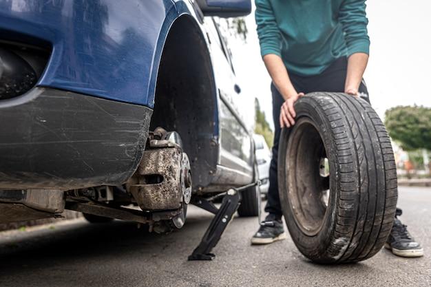 Meccanico che avvita o svita cambiando la ruota dell'auto con la chiave meccanica al lavoro cambiando una ruota su un'auto