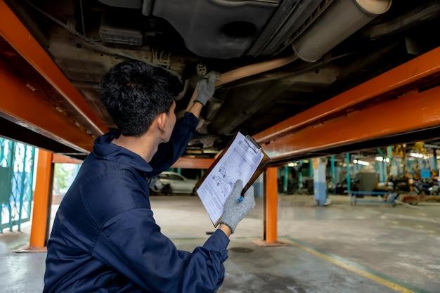Un'auto di servizio meccanico in garage è controllare un elenco di auto.