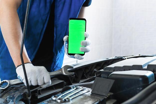 Un meccanico sta vicino a un'auto con il cofano aperto in garage e tiene in mano una chiave e uno smartphone
