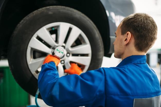 Il meccanico svita la ruota in servizio gomme