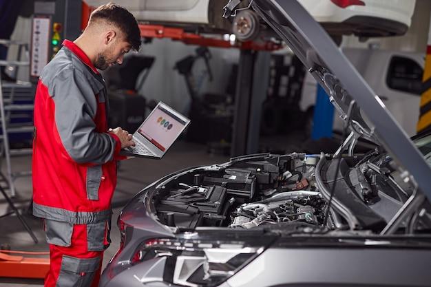 Meccanico che utilizza laptop e ispeziona l'auto in servizio