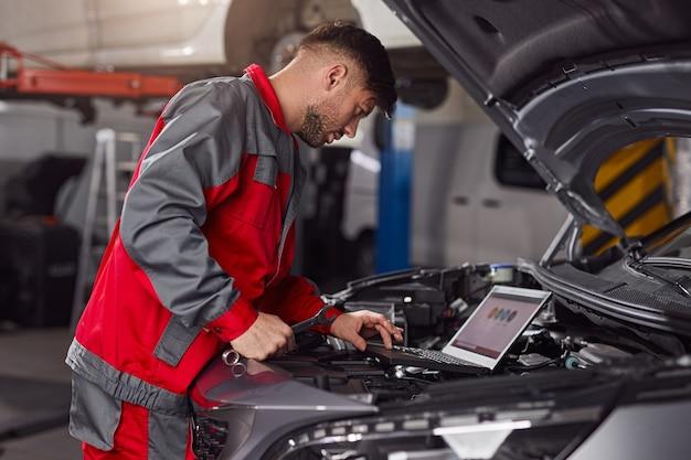 Meccanico utilizzando laptop durante la riparazione del motore del veicolo