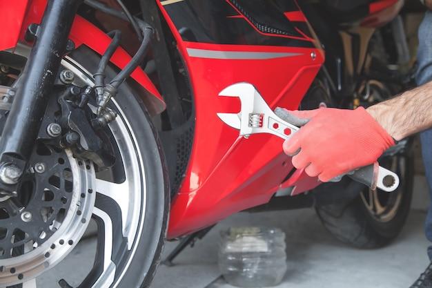 Meccanico utilizzando una chiave su una motocicletta. box auto. opera