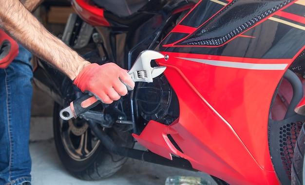 Meccanico utilizzando una chiave su una motocicletta