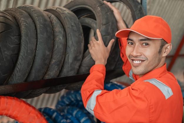 Il meccanico in uniforme wearpack guarda davanti mentre raccoglie pneumatici da un rack in un'officina di pezzi di ricambio per motociclette