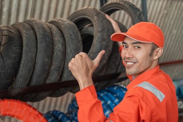Meccanico in uniforme wearpack con un pollice in alto mentre preleva un pneumatico da un rack in un'officina di ricambi per moto