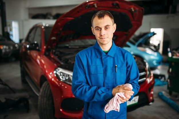 Il meccanico si asciuga le mani dopo aver riparato l'auto, diagnostica del motore.