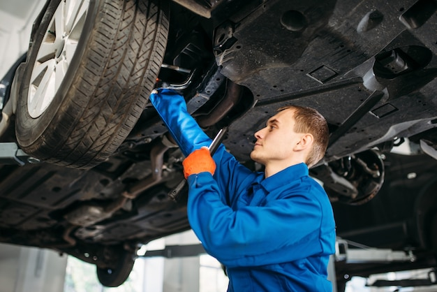 Il meccanico con la lampada controlla i tubi del freno dell'auto