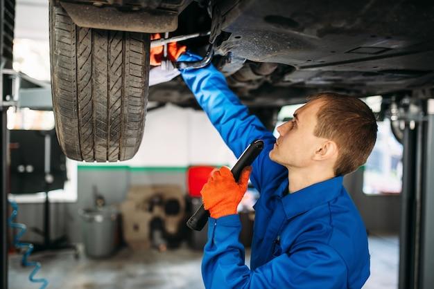 Meccanico con lampada controlla la sospensione dell'auto, stazione di riparazione.