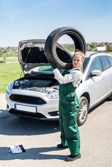 Meccanico con pneumatico e automobile rotta sul ciglio della strada