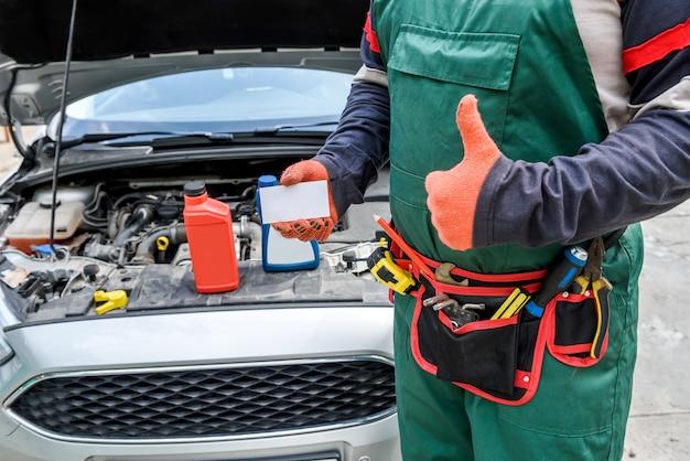 Meccanico con biglietto da visita in posa vicino all'auto con il cofano aperto