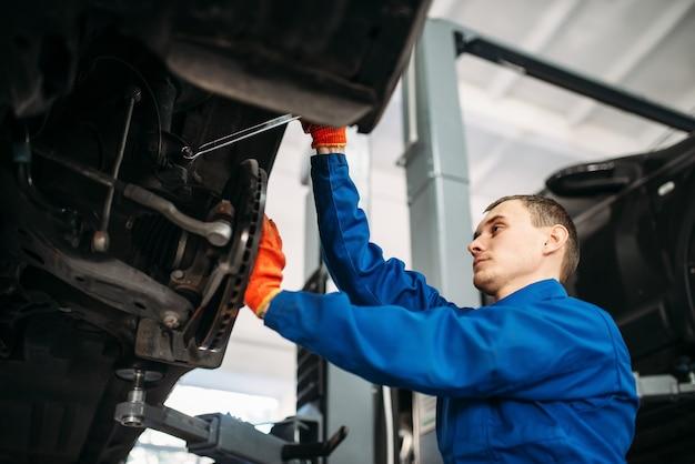 Meccanico con chiave ripara le sospensioni dell'auto