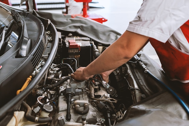 Meccanico di manutenzione auto funzionante con soft-focus e luce eccessiva sullo sfondo