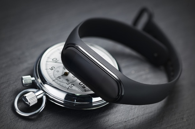 Cronometro meccanico e tracker fitness o attività su pietra nera. concetto di allenamento sportivo