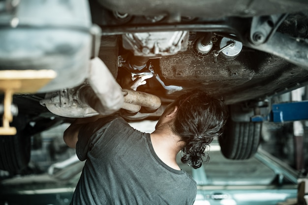 Meccanico che ripara automobile in garage sotto l'automobile.