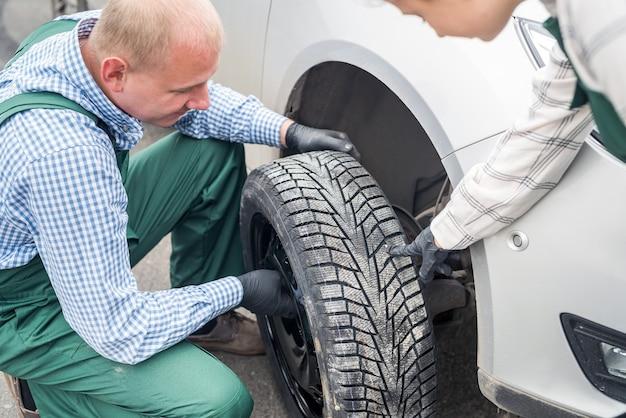 Meccanica che cambia ruota di un'auto al servizio