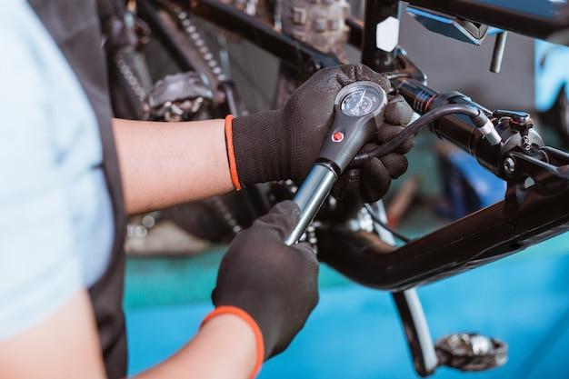 Una mano del meccanico nei guanti utilizza una pompa da bicicletta con un manometro per regolare la sospensione posteriore