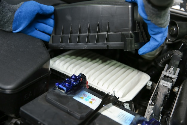 I meccanici con le mani nei guanti stanno cambiando il filtro dell'aria nell'auto