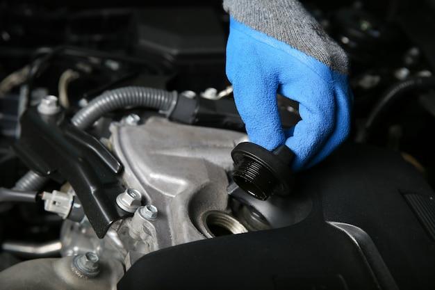 Le mani dei meccanici nei guanti stanno aprendo il tappo del bocchettone di rifornimento dell'olio nel motore dell'auto