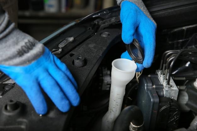 I meccanici con le mani nei guanti stanno aprendo il serbatoio del liquido lavavetri dell'auto
