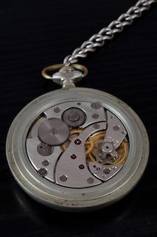 Meccanismo del vecchio orologio da tasca su sfondo nero