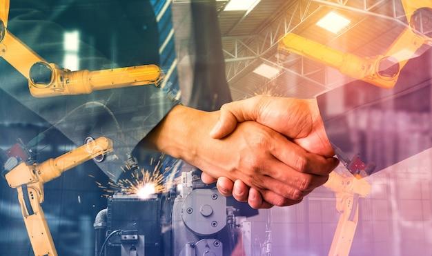 Braccio robotico industriale meccanizzato e stretta di mano aziendale doppia esposizione