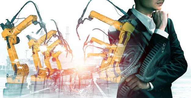 Braccio robot industriale meccanizzato e doppia esposizione operaio di fabbrica