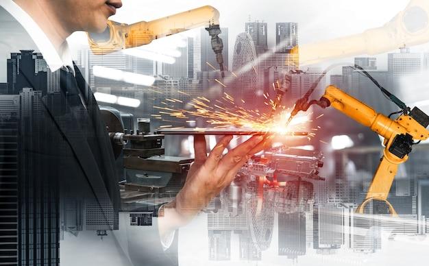 Braccio robotico industriale meccanizzato e doppia esposizione dell'operaio Foto Premium