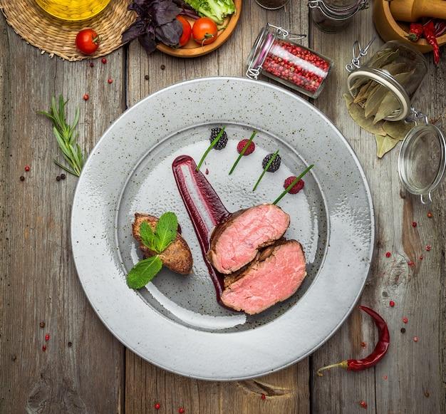 Medaglioni di vitello, con salsa su un piatto. fondo in legno