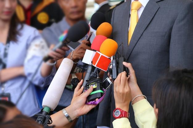 Intervista mediatica conept.gruppo di giornalisti che tengono il microfono per intervistare vip