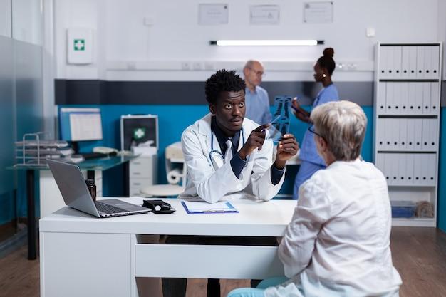 Medico di etnia afroamericana che tiene la scansione a raggi x