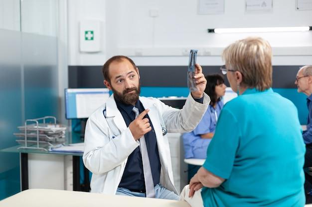 Medico che indica alla radiografia per l'esame di osteopatia