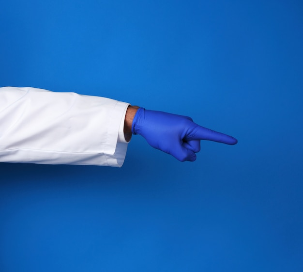 Medico in camice bianco, indossando guanti sterili blu, mostrando il gesto della mano che indica il soggetto, sfondo blu