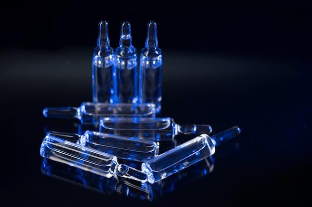 Fiale mediche con vaccino per iniezioni sul tavolo lucido scuro con spazio di copia