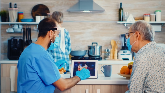 Assistenza medica che punta all'immagine del coronavirus su tablet pc durante la visita domiciliare. infermiere assistente sociale presso una coppia di anziani in pensione visita che spiega la diffusione del covid-19, aiuto per le persone nel gruppo a rischio