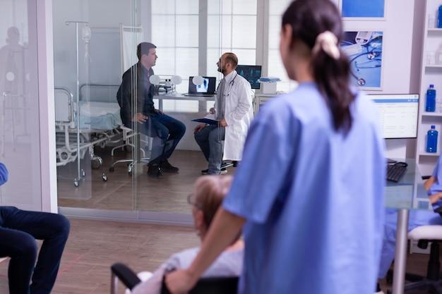 Assistente medico che aiuta una donna anziana handicappata, paralizzata e disabile in sedia a rotelle ad entrare nella sala d'esame per la consultazione. dottore che discute in background con un giovane paziente
