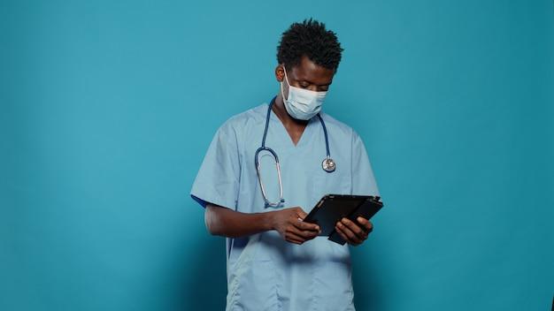 Assistente medico che utilizza tablet digitale indossando la maschera facciale
