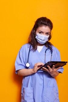 Assistente medico che indossa una maschera facciale utilizzando un dispositivo digitale