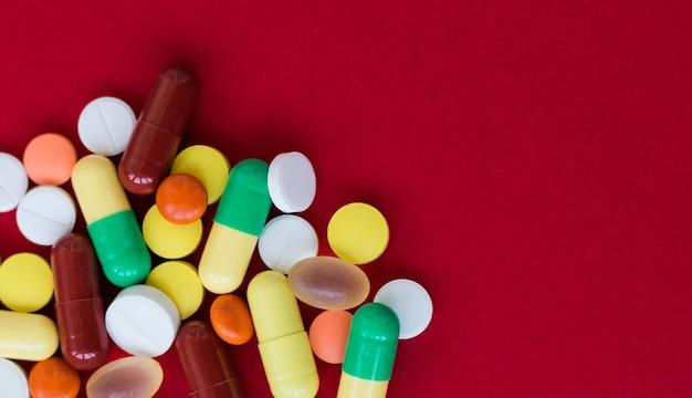 Sfondo medico con pillole e capsule su sfondo rosso.