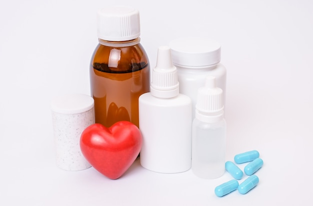 Bottiglie mediche piccolo cuore rosso e capsule blu-chiaro su copyspace sfondo bianco isolato