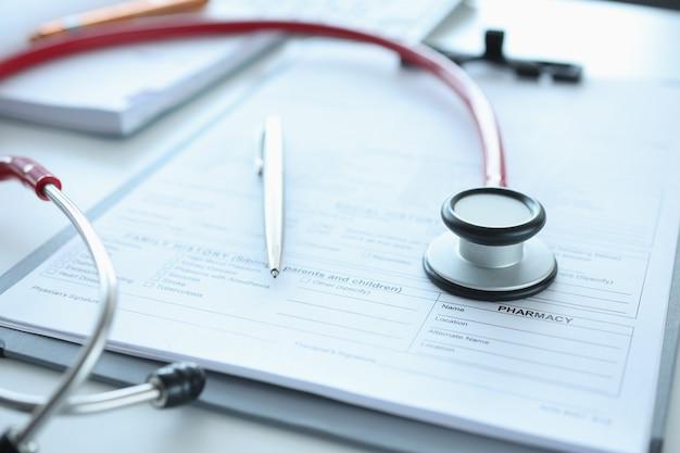 Penna e stetoscopio della tessera sanitaria sul concetto di risultati dell'esame medico del tavolo
