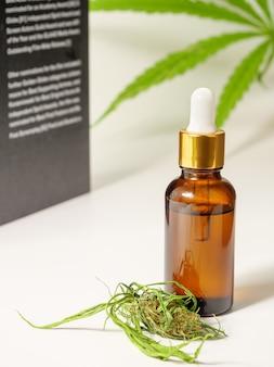 Estratto di olio di canapa cbd medico. foglia di cannabis fiore e libro su superficie bianca, concetto di ricerca medica