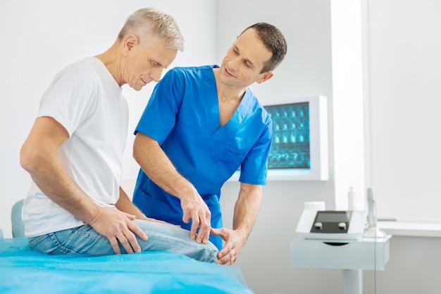 Controllo medico. uomo invecchiato piacevole serio che esamina il suo ginocchio e che racconta la sua sensazione durante il controllo medico